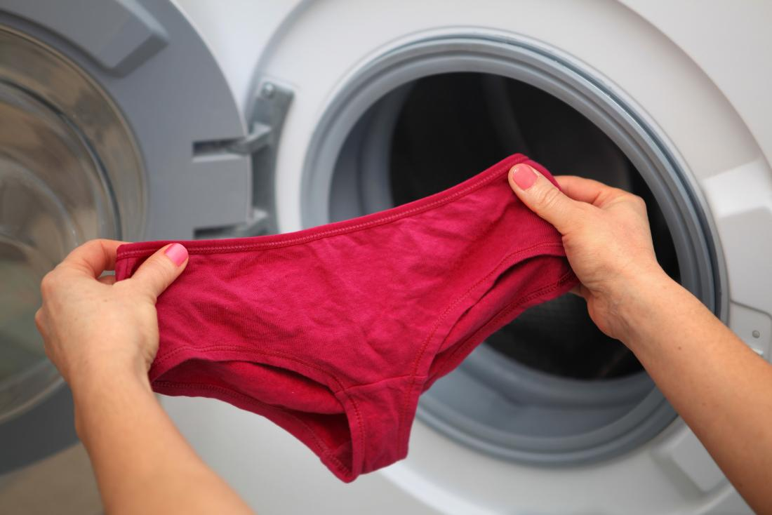 woman-holding-a-pair-of-cotton-underwear-pants-next-to-washing-machine
